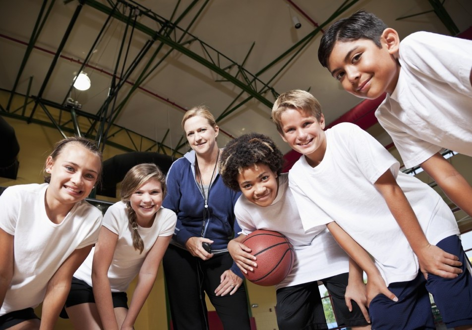 Multi-ethnic elementary or middle school students in school gym with coach playing basketball.